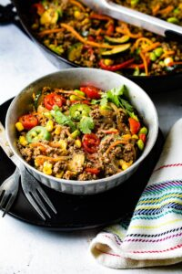 A bowl of taco pasta. The pasta contains corn, zucchini, jalapenos, tomatoes, pasta, and ground beef.