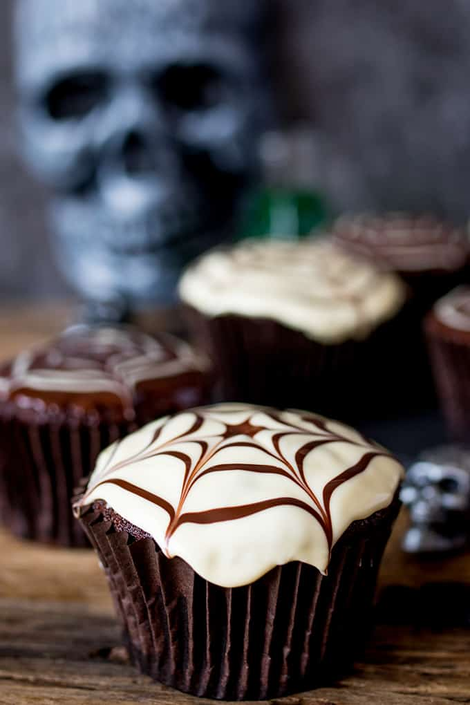 Close up of a chocolate Halloween cupcake with a spiderweb pattern on top.