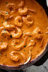 A flavour-filled shrimp curry with an aromatic coconut curry sauce cooks in no time from scratch! Shrimp curry in a black skillet with a metal serving spoon | cafedelites.com