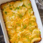 Easy scalloped potatoes in casserole dish garnished with chives